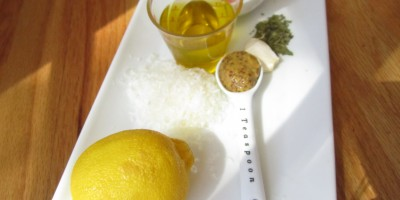 Ingredients for homemade Zesty Italian Dressing: lemon, mustard, parmesan, oregano, basil, olive oil, garlic clove